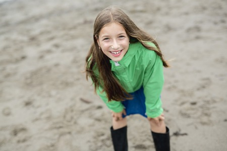 beach rain: A Girl enjoying the rain and having fun outside on the beach on a gray rainy