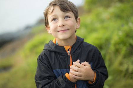 A boy close to the grass at sunset Stock Photo