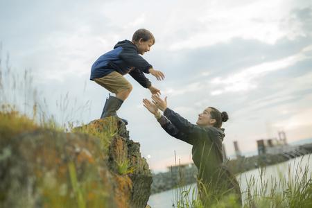 Una madre che aiuta i bambini a saltare giù dalle rocce Archivio Fotografico
