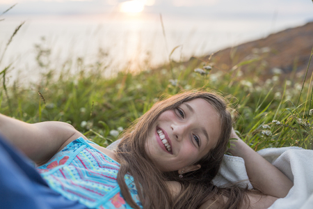 A Teenager girl at sunset on the side of the sea
