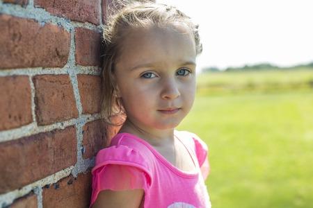 A Worried little girl brick house outside Foto de archivo