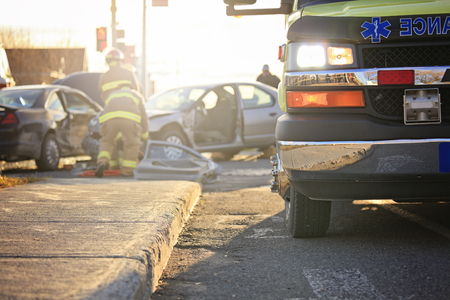 An accident scene on the road of a city with ambulance and fire fighter.