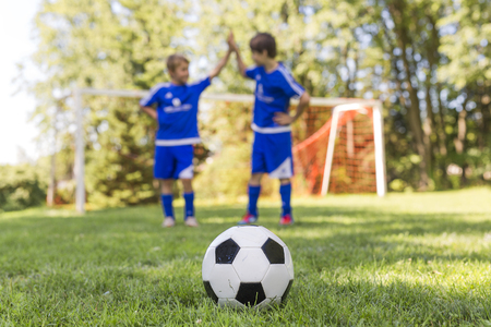 Two Young boy with soccer ball on a sport uniform