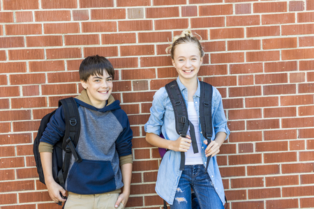 A Portrait of school 10 years boy and girl having fun outside Stock Photo