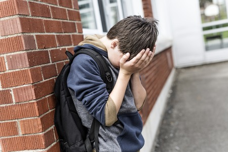 A Unhappy depress Pre teen boy at school