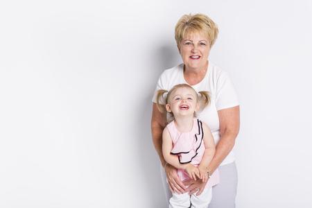 明るい背景に孫を持つ祖母 写真素材