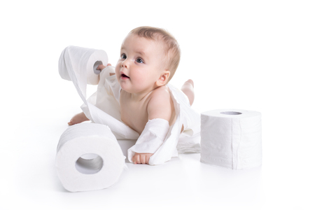 Toddler ripping up toilet paper in bathroom studio Stock Photo