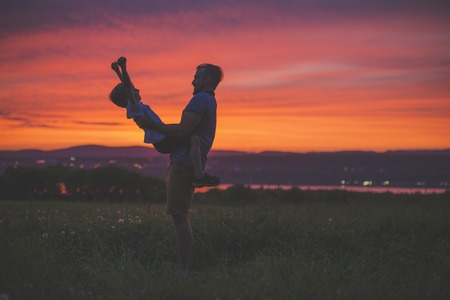 silhouette of father and son at sunset having fun
