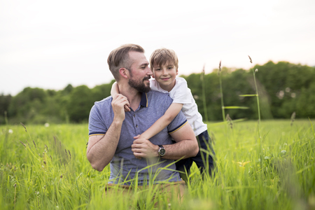 A Father and son having fun outdoors in the meadow Stock Photo