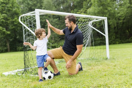 father with son playing football on football pitch Stock Photo