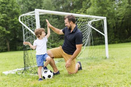 vader en zoon voetballen op voetbalveld