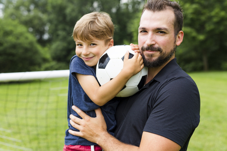 A father with son playing football on football pitch Stock fotó
