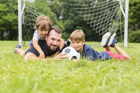A father with son playing football on football pitch Stock Photo