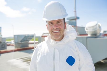 radiation protection suit: A professional in protective uniform, in the roof for cleaning