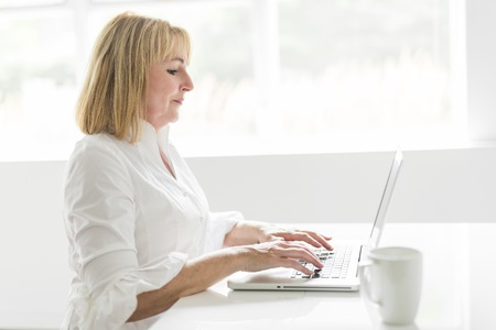 A mature woman using laptop at home Stock Photo