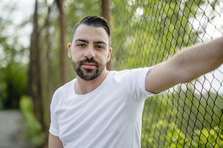 A pretty men standing near chain link fence Stock Photo