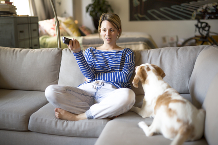 woman sitting on the couch take some good time with his dog