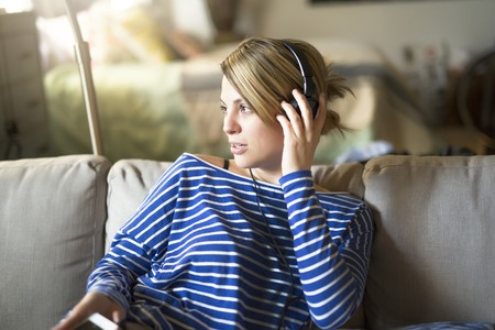 woman sitting on the couch take some good time with music headphone,