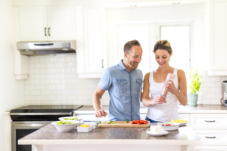 couple in the kitchen doing salad together Imagens