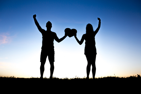 Romantic young couple holding heart shape on hands at sunset