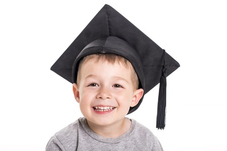 Adorable four years old child boy wearing a mortar board. Stock Photo