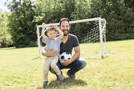 Young father with his little son playing football on football pitch Stock fotó