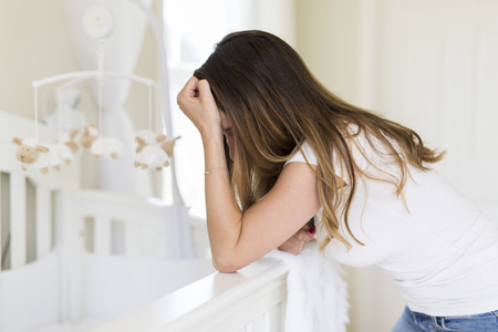 Depressed young woman in baby room