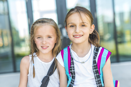 Two girls Standing Outside School With Book Bags