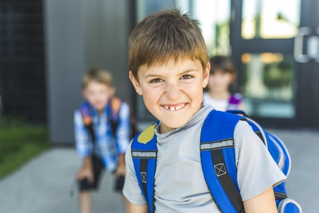 Boy Standing Outside School With Bag