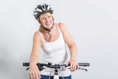 senior woman on the side of a bike in studio white background Stock Photo