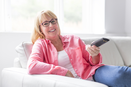 Mature attractive woman with a remote control on TV