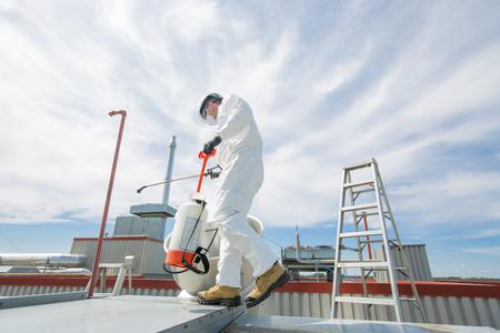 Profi in Schutzkleidung, Maske, Handschuhe im Dach zur Reinigung