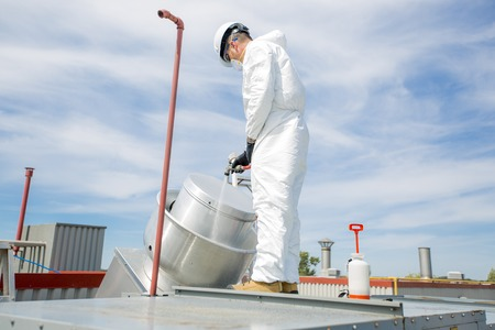 professional in protective uniform, mask, gloves in the roof for cleaning Stock Photo