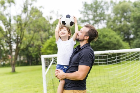 father with son playing football on football pitch Stock fotó