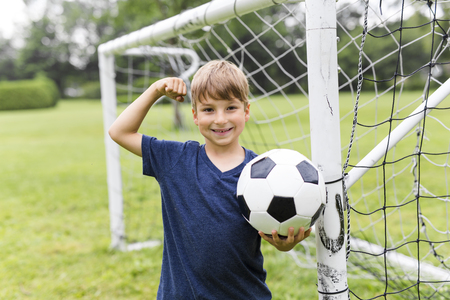 Young Boy with football on a field having fun Stock Photo