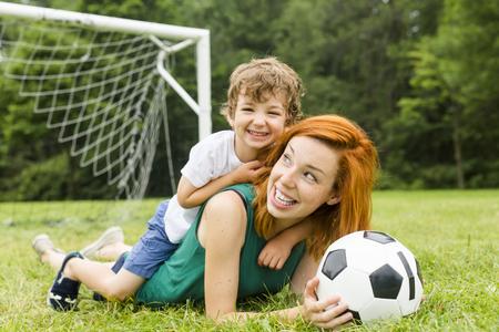Afbeelding van familie, moeder en zoon bal in het park spelen
