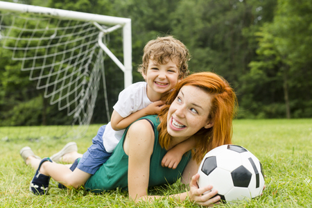Image of family, mother and son playing ball in the park Foto de archivo