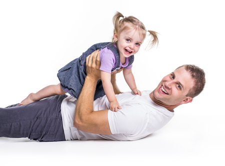 Father and daughter lay on ground having fun