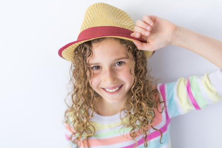 Portrait of 9 years old girl with curly hair, isolated on gray Stock Photo