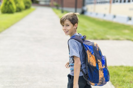 Great Portrait Of School Pupil Outside Classroom Carrying Bags Stock Photo