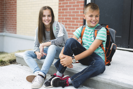 Portrait of two school friends with backpacks