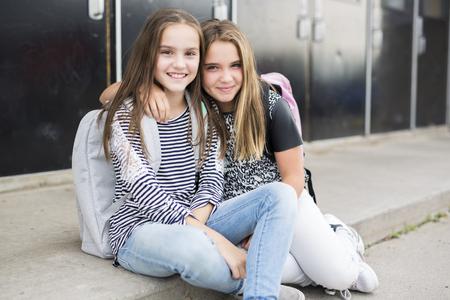 Portrait of two pre teenage girls studying outdoors in school yard