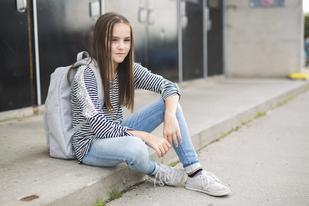 Elementary school pupil outside carrying rucksack