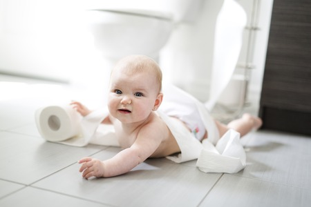 幼児がトイレでトイレット ペーパーを裂く 写真素材