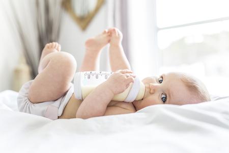 Het mooie babymeisje drinkt water van fles liggend op bed. Kind weared luier in kinderkamer. Stockfoto