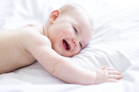 La neonata in biancheria da letto bianca a casa sembra piacevole Archivio Fotografico - 86435851