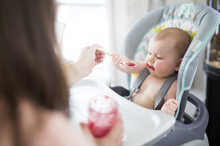 Mother Feeding Baby girl In High Chair Stock Photo