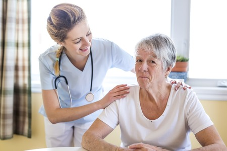 Senior woman with her caregiver at home Stockfoto