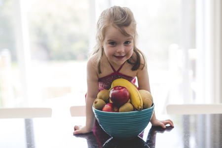 Happy girl with a bowl of fruits at home Zdjęcie Seryjne