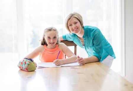 Mother helping teenaged girl with homework
